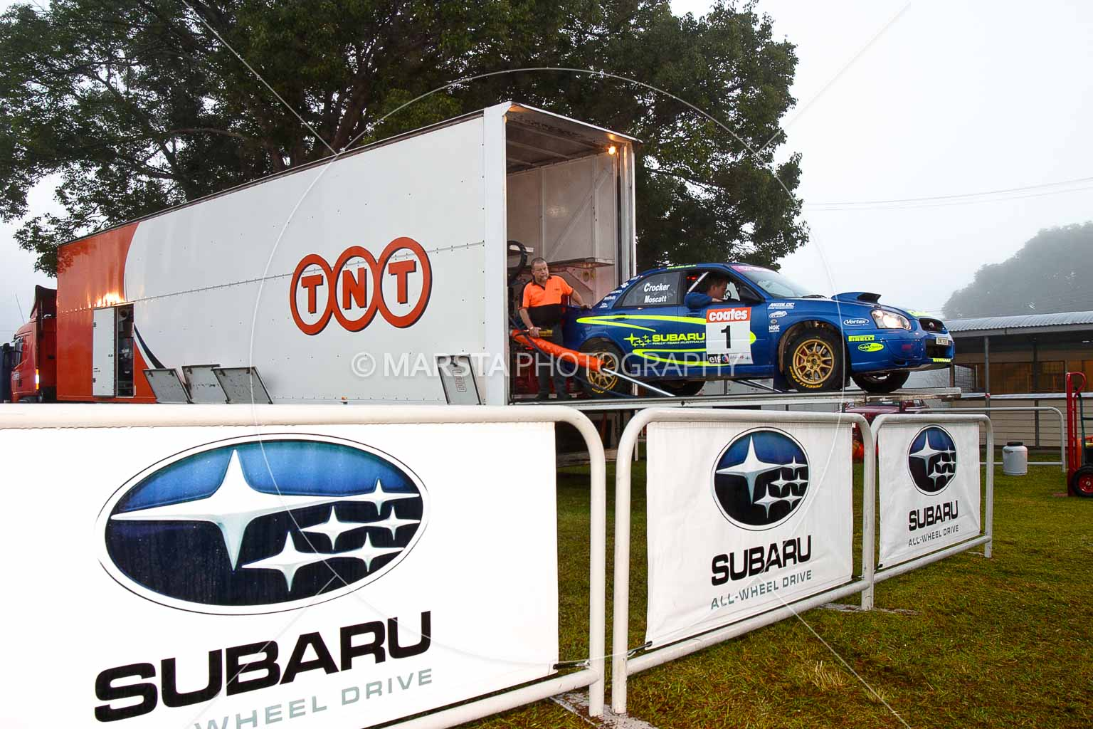 (1);050605ARC;4 June 2005;ARC;Australia;Australian Rally Championship;Coates Rally Queensland;Imbil;QLD;Queensland;Subaru Impreza WRX;Sunshine Coast;auto;crew;mechanics;morning;motorsport;racing;service park;transporter;wide angle